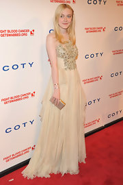 Dakota Fanning carried this delicate gold box clutch with her to the DKMS Gala.