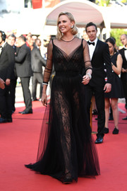 Charlize Theron was a head turner in a sheer black tulle and lace gown by Christian Dior Couture at the Cannes Film Festival 70th anniversary event.