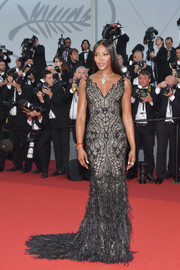 Naomi Campbell looked ageless in a figure-hugging Atelier Versace gown, featuring black embroidery and feather embellisments on a nude background, at the Cannes Film Festival 70th anniversary event.