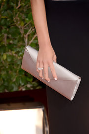 Olivia Munn carried a cream satin clutch on the red carpet.