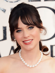 Zooey Deschanel paired her crimson ballgown with a strand of pearls.