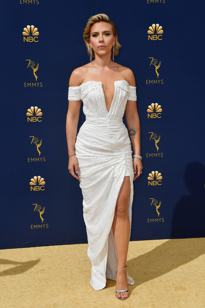 Scarlett Johansson looked alluring at the 2018 Emmys in a white off-the-shoulder dress with a plunging neckline and a thigh-high slit.