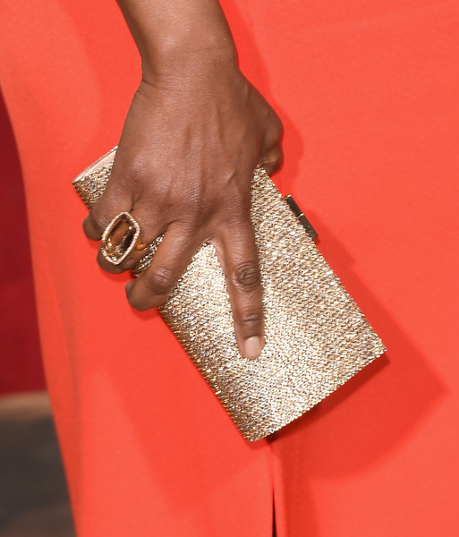 Angela Bassett's gold sequin clutch complemented her orange dress at the 2016 Golden Globes Awards.