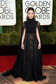 Emilia Clarke was goth-glam in a caped black empire gown by Valentino at the Golden Globes.