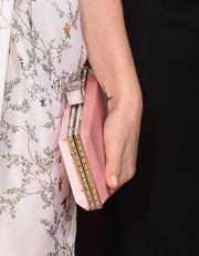 Melissa Benoist styled her soft pink clutch to match her delicate gown at the 2016 Golden Globes Awards.