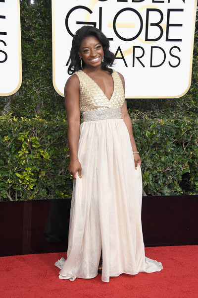 Simone Biles attended the Golden Globes looking like a goddess in a metallic gown with a plunging neckline and a bedazzled waistband.
