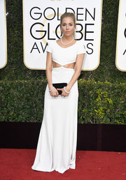 Sienna Miller styled her dress with a black satin clutch by Christian Louboutin.