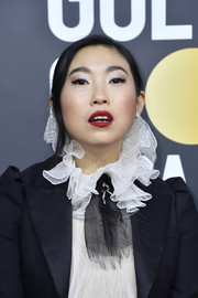 Awkwafina paired a bold red lip with a cat eye for her beauty look.