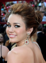 Miley Cyrus topped off her elegant hairstyle with dangling gemstone earrings with ruby and diamonds.