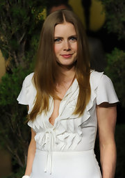 Amy Adams styled her long locks in a sleek center part hairstyle.
