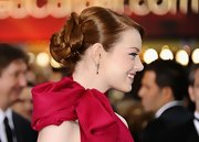 Emma Stone attended the 84th Annual Academy Awards wearing her copper locks in a sleek updo featuring loose pinned-up curls.