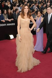 Kristen Wiig opted for a feminine look in a tiered ruffled dress paired with simple tousled waves.