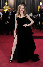 Angelina Jolie and her now famous right leg made a grand entrance at the Oscars in a velvet strapless gown with a revealing slit.