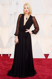 Margot Robbie went for boudoir glamour in a sheer-sleeve, draped black wrap gown by Saint Laurent during the Oscars.