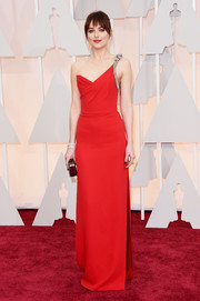 Dakota Johnson attended the Oscars looking like a goddess in a red Saint Laurent one-shoulder gown with a bedazzled strap and a thigh-high side slit.