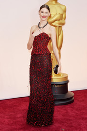 Behati Prinsloo attended the Oscars wearing a richly appliqued red and black strapless gown by Armani Prive.