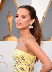 Alicia Vikander glammed up her 'do with a pair of diamond chandelier earrings by Louis Vuitton.
