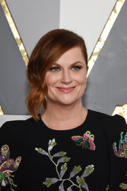 Amy Poehler attended the Oscars wearing a loose bun with wavy tendrils cascading down one side.