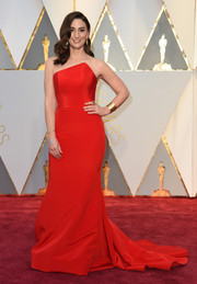 Sara Bareilles chose a strapless red Romona Keveza gown, featuring an asymmetrical neckline and a long train that the singer paired with Marco Bicego jewelry and Aquatalia shoes for the 2017 Oscars.