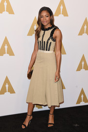Naomie Harris kept it carefree yet chic in a beige Bottega Veneta midi dress with black accents at the Academy Awards nominees luncheon.