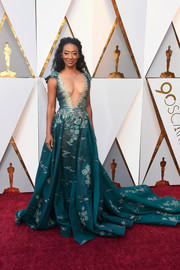 Betty Gabriel wowed in an embroidered teal Tony Ward Couture gown with a plunging illusion neckline at the 2018 Oscars.