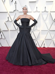 Lady Gaga went for goth glamour in a strapless black gown and matching leather gloves at the 2019 Oscars.