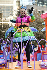 JoJo Siwa contrasted her colorful coat with plain black leggings.