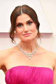 Idina Menzel styled her hair into a loose center-parted bun for the 2020 Oscars.