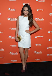 Shay livened up her little white dress with this gold knuckle-duster clutch.