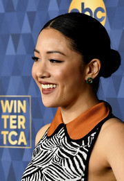 Constance Wu accessorized with a pair of tiny green hoops.