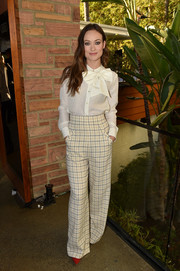 Olivia Wilde wears a chic, button-down long-sleeved white pussybow blouse to the AFI Fest