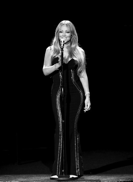 Mariah Carey flaunted her curves in a form-fitting lace-up gown by Georgine at the AHF World AIDS Day concert.
