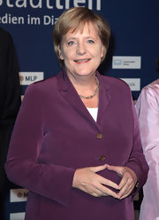 Politician Angela Merkel wears her hair in a cropped side-part with front bangs.