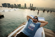 Janko Tipsarevic relaxed at the Infinity Pool at Marina Bay Stands while wearing a graphic Fila T-shirt.