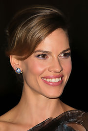 Hilary Swank highlighted her side swept bun with decadent gemstone stud earrings while attending the Second Annual Governors Awards. She added a little sparkle to her look with a swipe of lilac eyeshadow.