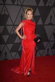 Juno Temple styled her gown with a black satin clutch by Tyler Ellis.