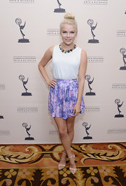 Kelli Goss kept her look fun and flirty by pairing this simple sleeveless white blouse with a purple floral skirt.