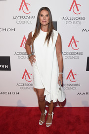 Brooke Shields matched her dress with a pair of white ankle-strap sandals, also by Calvin Klein.