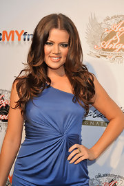 Khloe adds some curls to her long brown locks at the celebrity poker party. Her long flowing curls pull together her glamorous look.