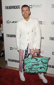 Perez Hilton showed off his turquoise Longchamp telephone-print tote at the Advocate's 45th anniversary.