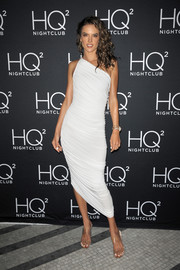 Alessandra Ambrosio flaunted her shapely figure in a ruched white one-shoulder dress by Norma Kamali at the HQ2 Beachclub event.