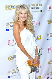 Christie Brinkley paired a printed clutch with a white one-shoulder jumpsuit for the Bella New York beauty cover launch.