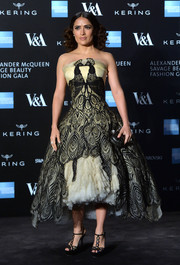 Salma Hayek displayed no shortage of frill at the Savage Beauty exhibition in an Alexander McQueen strapless frock boasting a dramatic fit-and-flare silhouette, lace peacock detailing, and a thick tulle petticoat.