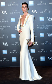 Erin O'Connor looked absolutely arresting in a sleek white Alexander McQueen gown, featuring a figure-hugging silhouette and a satin-trimmed, plunging neckline, during the Savage Beauty exhibition.
