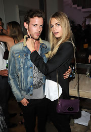 Cara Delevingne carried a chain strapped swing pack at the All Saints 'Not For Sale' launch party.