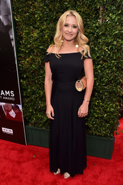 Emily Osment added some shine to her look with a gold tube clutch.