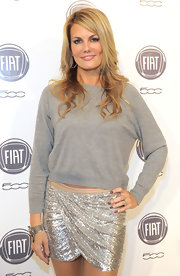 Courtney rocked a super silvery mini sequined skirt with toga like draping with a casual gray sweater.