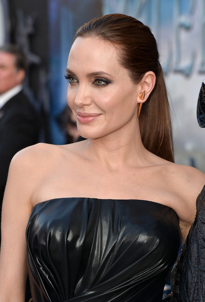 Angelina Jolie Gold Studs [red carpet,hair,beauty,fashion model,human hair color,hairstyle,eyebrow,shoulder,long hair,fashion,black hair,angelina jolie,maleficent,california,hollywood,el capitan theatre,disney,world premiere]