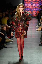 Gigi Hadid walked the Anna Sui runway wearing a shiny red tunic dress.