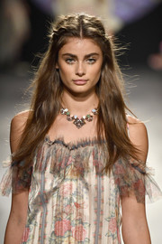 Taylor Hill sported a colorful gemstone necklace to match her floral frock.